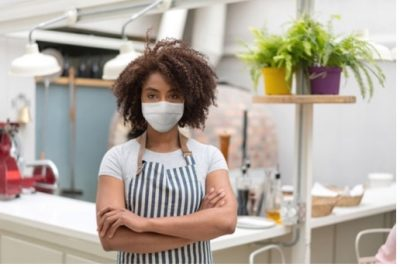 picture of female business owner in a mask with crossed arms