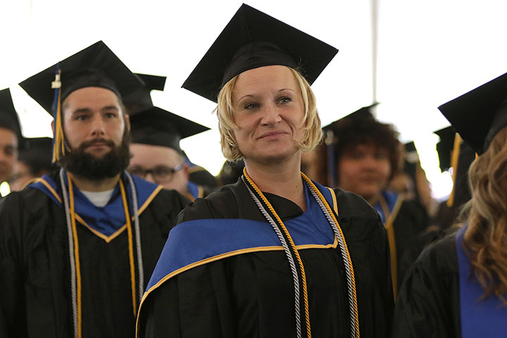 A female graduate looks on smiling, a male grad behind her also looks on.
