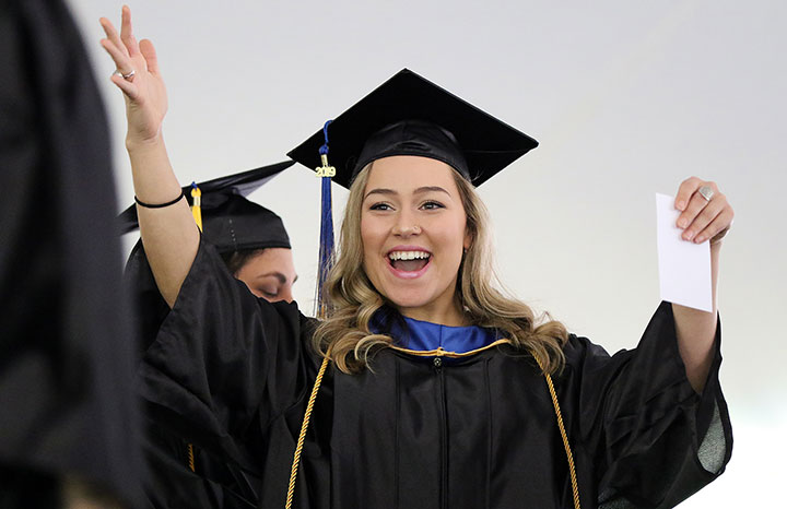 A Happy female grad with arms raised, and with huge smile,