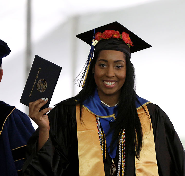 A female honors grad holding up her degree, and smiling.