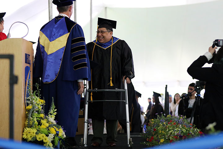 A happy male graduate, comes to the podium (with assitance of a walker), to recieve his degree from President Glenn.
