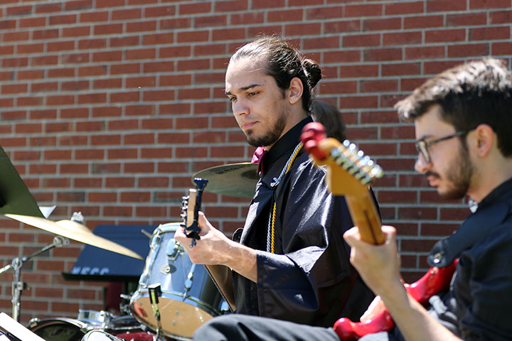 A male graduate, in graduation regalia, playing guitar in a band outside.