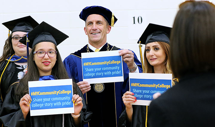 """President Lane Glenn with two female grads hold up signs """"#MYCommunityCollege Share your community college story with pride!"""""""