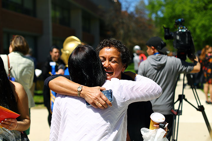 Two happy women hug during the Commencement pre-event.