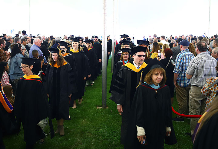 two lines of Faculty and Staff in commencement regalia, walking to their seats.