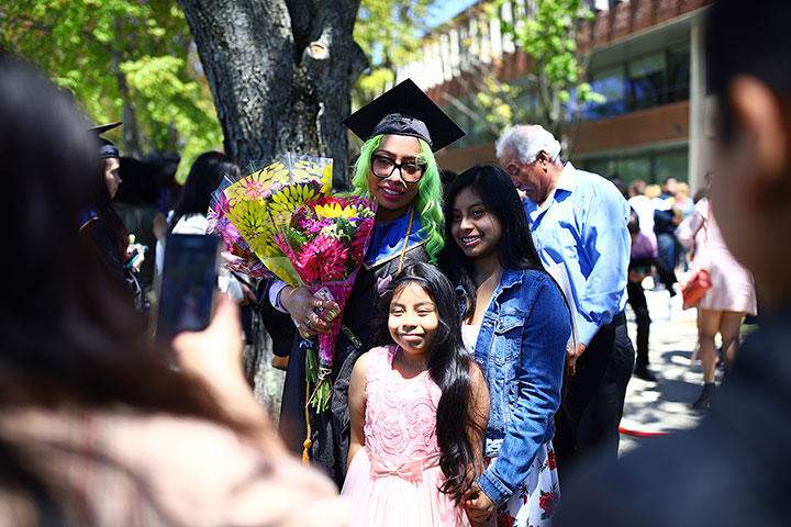 A female gradute, in gradualtion regalia, holding flowers and two children in front of her.