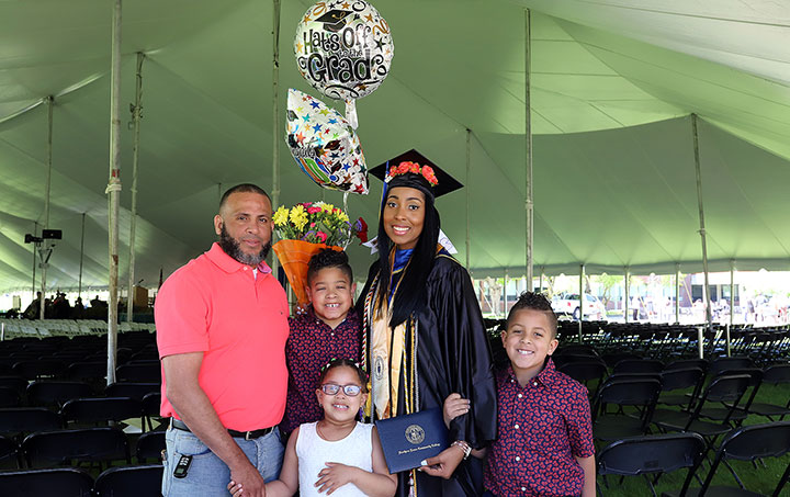 A female grad holding balloons, flowers and her degree, surrounded by three children, and an adult male.