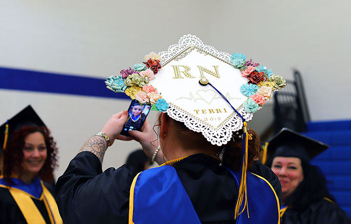 """A student's graduation cap decorated with a lace and flower outline and the words """"RN, Terri 2019"""""""