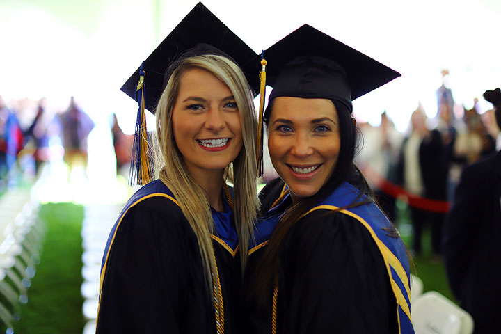 Two happy female grads pose for the camera, face to face.