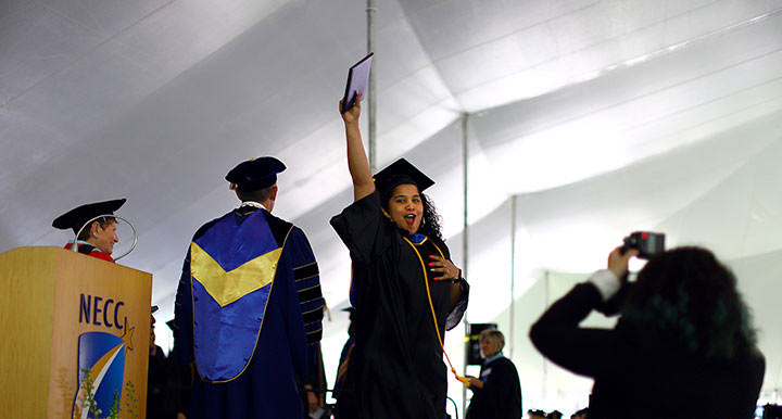 A female student that just recieved her degree thrusts it in the air and cheers for joy.
