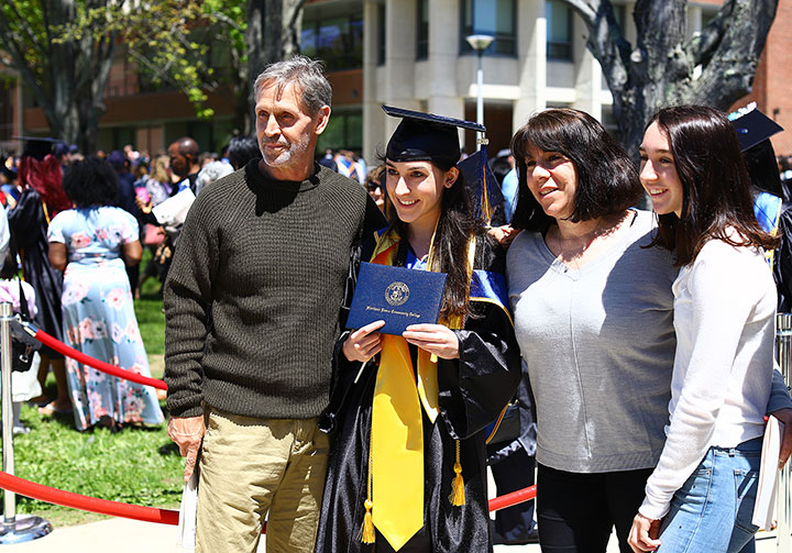 A female grad outside, holding up her degree, surrounded by family