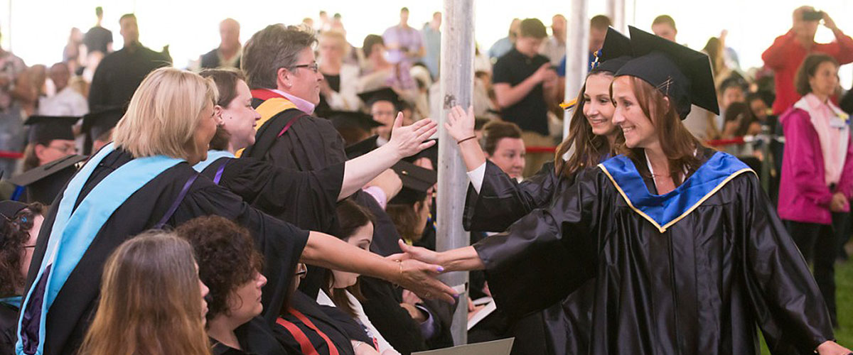 A line of graduating students walking, with the first woman shaking hands with people in the audience.