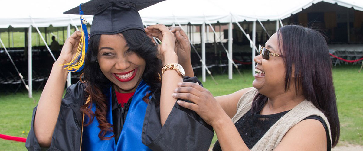 A student dressed in regalia fixes her capwith her friend's help. Both happy and smiling.