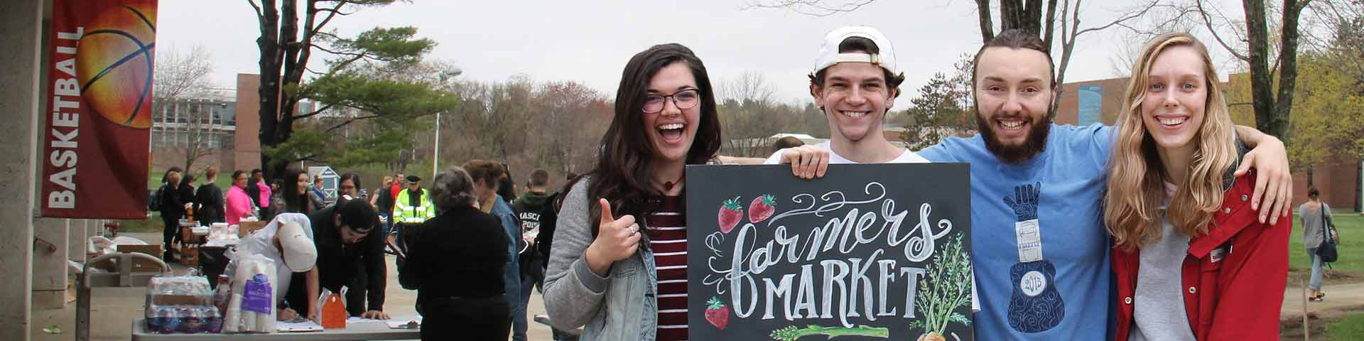 Four NECC students outside at a Farmer's Market, happy, and standing arm-in-arm holding up a sign for the market.