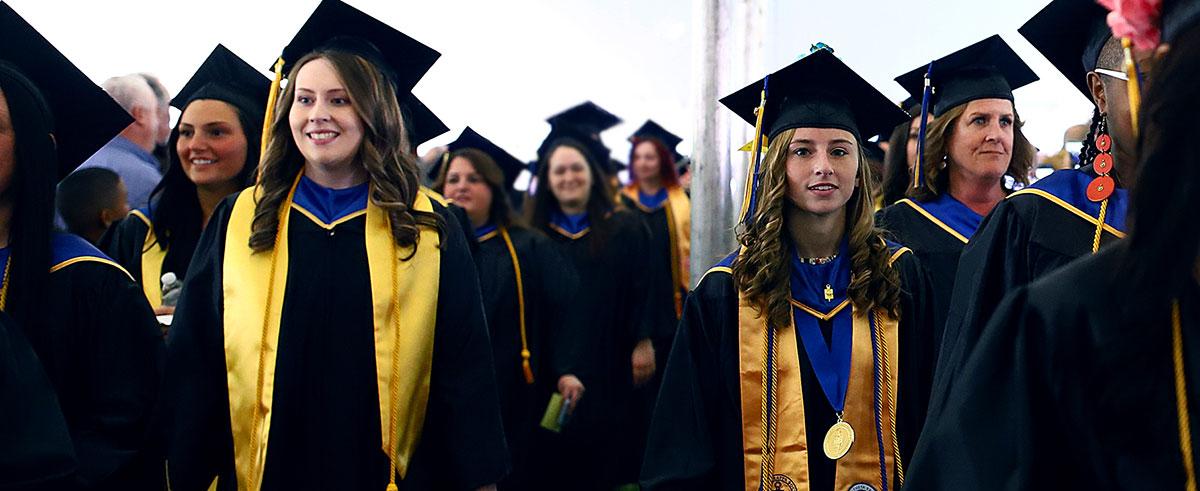 Two lines of Graduates, in graduation regalia, walking down the aisle.