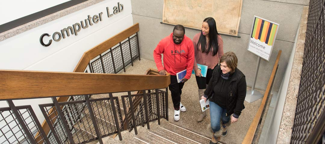 Three students walking the stairs to the Computer Labs. Welcome sign behind.