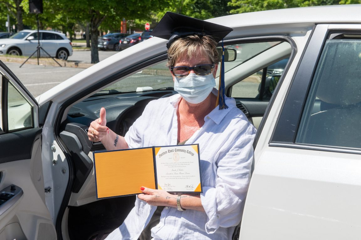 Female graduate receives diploma and celebration package while in car, 2020 graduation.