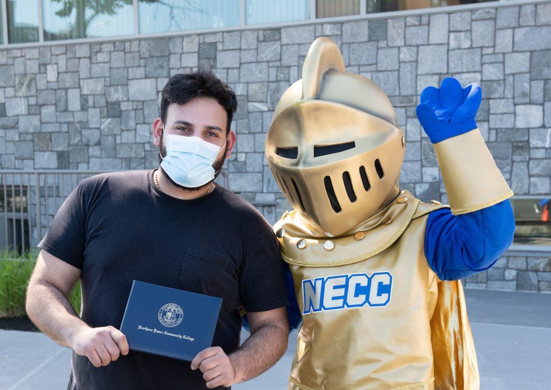 Male graduate holding diploma standing next to NECC knight. 2020 Graduation.
