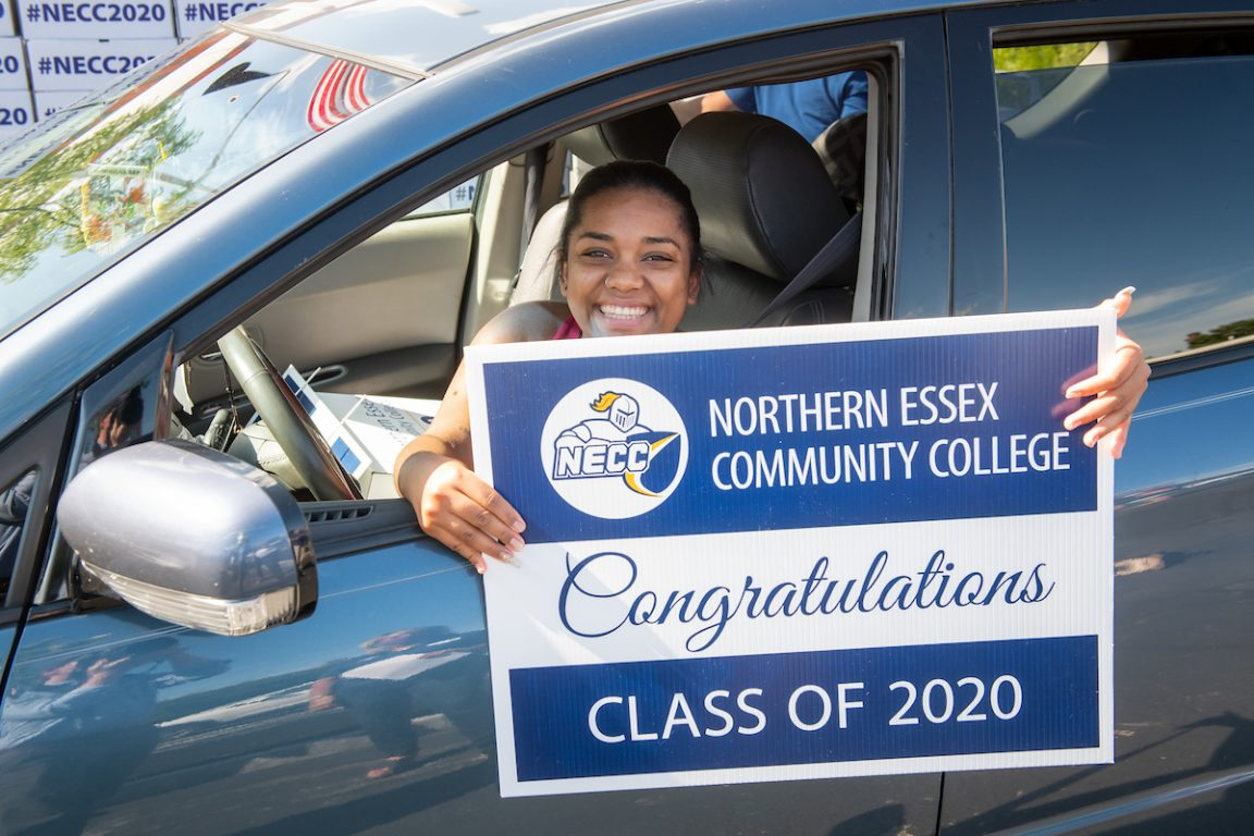 Female graduate in car holding graduation sign. 2020 graduation.