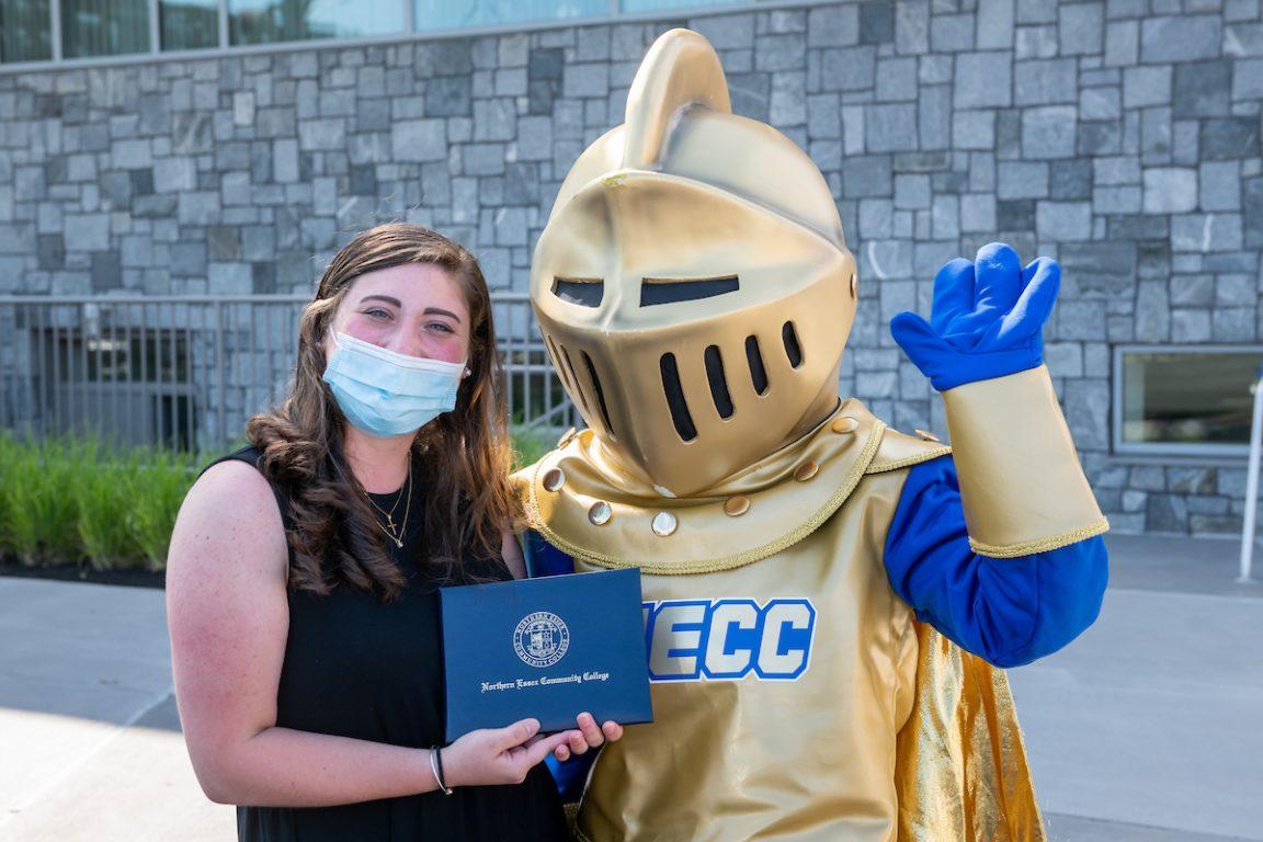 Female graduate holding diploma standing next to NECC knight. 2020 Graduation.