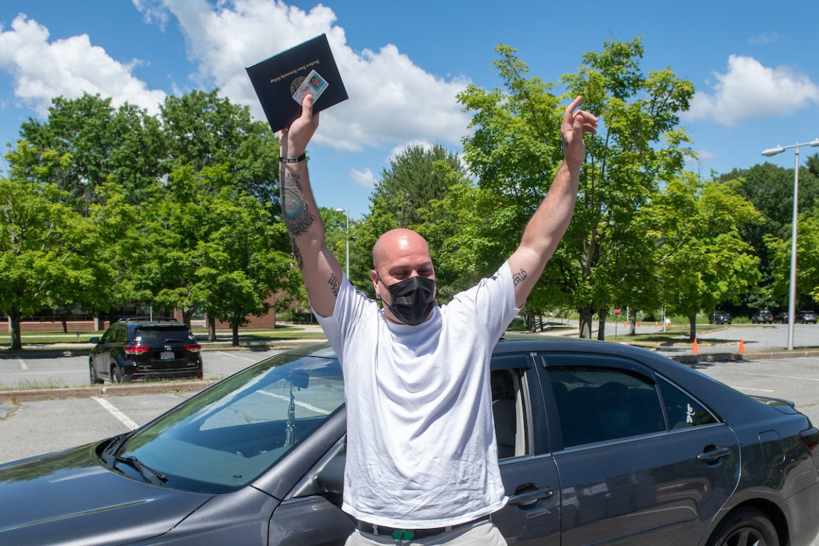 Male graduate receives diploma and celebration package, 2020 graduation.