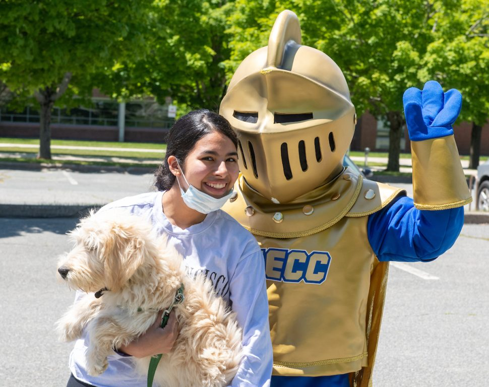 Woman holding dog stands next to NECC knight. 2020 graduation.