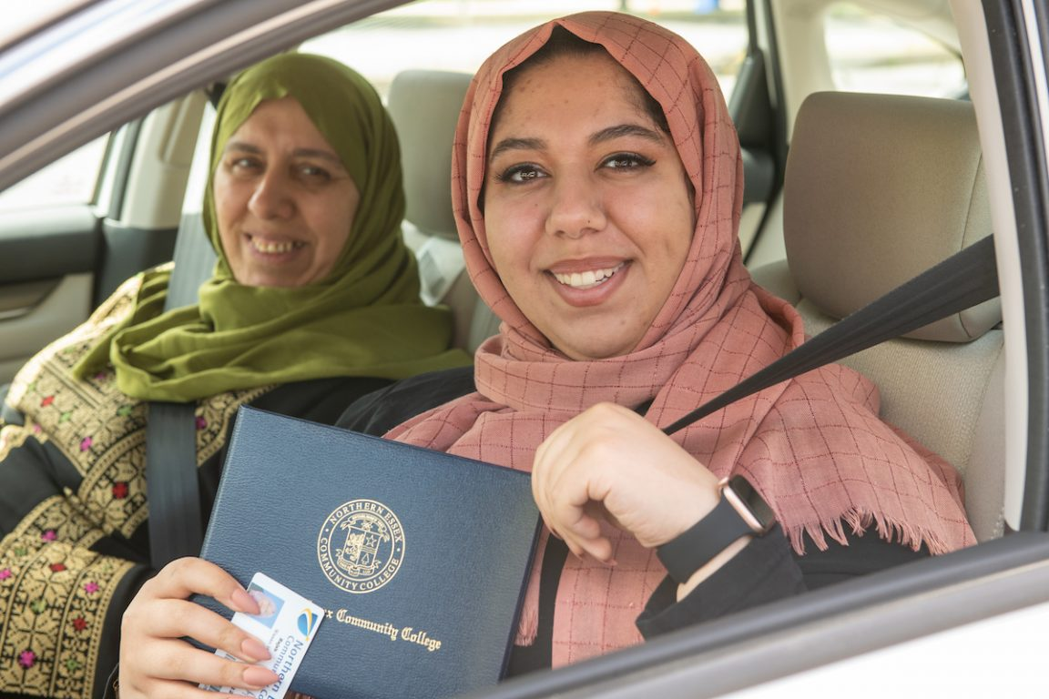 Two smiling women in car, one hold diploma. 2020 graduation.