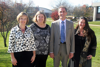 NECC employees Rebecca Rose, Trisha Foster, and Diana Mele photographed with NECC President Lane Glenn