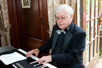 "Phil Porter ""the Pino Man"" sitting at the piano keyboard."