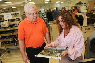 Gina Whittier of Lightspeed Manufacturing shows Haverhill City Council President John Michitson one of the company's circuit boards.