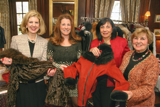 Models for Dino International Furs, Joanne Dee and Mary Tyrrell, both of Andover, Anne Mantsios of Dino International Furs, and Gerri Murphy of North Andover admire a few of the items modeled during the Women of NECC's holiday luncheon and fashion show.