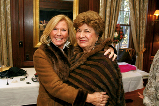 Jeannie Scarpa of Andover and Gloria Kirsch of Methuen strike a pose while modeling furs For Dino International Furs during the Women of NECC's holiday luncheon and fashion show which raises money for scholarships.