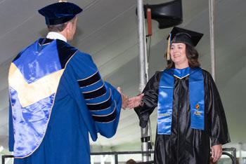 Alice Beauchamp of Newburyport receives diploma from NECC President Lane Glenn.