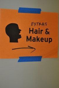 A sign shows movie extras where to report for hair and makeup.