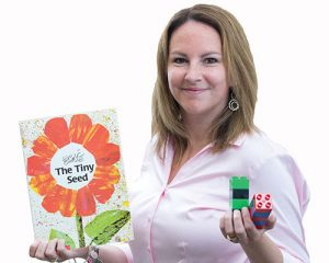 Jody Carson holding an Eric Carle Book and some legos.