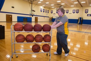 Brett rolls the basketball rack onto the court in preparation for the NECC home game.