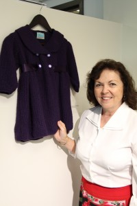 Susan Fichera exhibits a child's smock coat with satin ribbon that she knit.