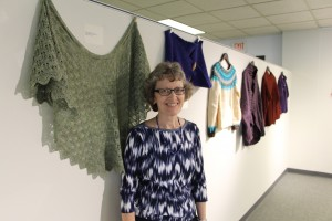 Lynne Nadeau, organizer of the NECC Fiber Arts Exhibit, stands in front of the leaf lace shawl she knit.