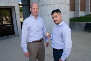 Veterans Services coordinator Jeffrey Williams (left) hands NECC U.S. Army Veteran and recent NECC graduate a challenge coin.