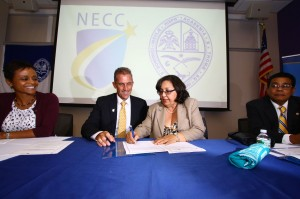 Lane Glenn, NECC president, and Clara Benedicto, USAD director of cooperation and international relations, sign agreement, watched by Noemi Custodia-Lora, NECC (left in photo) and Julio Sepulveda, USAD (right in photo).