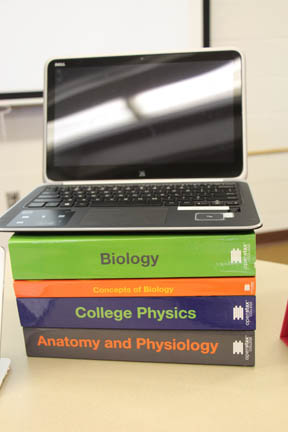 Laptop computer stacked on top of four text books