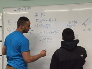 Methuen resident and NECC student Caros Rrivera, who is a student assistant in the Student Success Center, reviews a math problem with a student.
