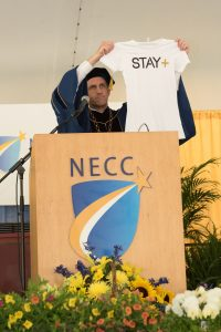 NECC President Lane Glenn exhibits a Stay+ tshirt which is the creation of graduate CJay DiPrima.