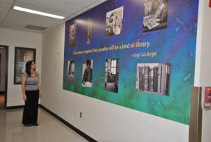 "NECC Lawrence Librarian Jennifer Fielding looks at ""The Library"" mural that was installed outside the information literacy lab."