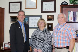 NECC President Lane Glenn, congratulates NECC employees Nancy Carroll, and Larry Rickabaugh.