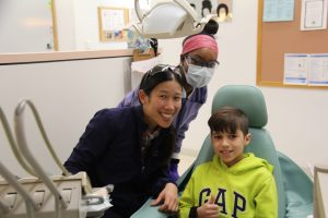 Dental patient Gustavo Rocha sits in a chair, giving the thumbs-up sign, while Dr. Bridget Ko and NECC student Rosa Livingston stand off to the left.
