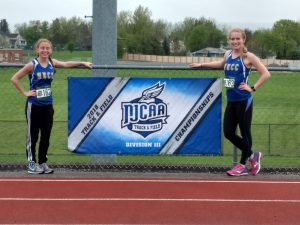 Olivia Mullins and Katelyn Richardson standing on the track by the NJCAA championship banner.