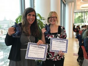 Kristen Sparrow and Clare Thompson smile holding their COD award and certificates