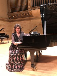 Christina Dietrich sits in a long dress at a Steinway piano
