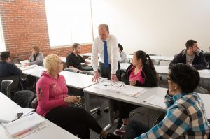 Students and professor have conversation in classroom